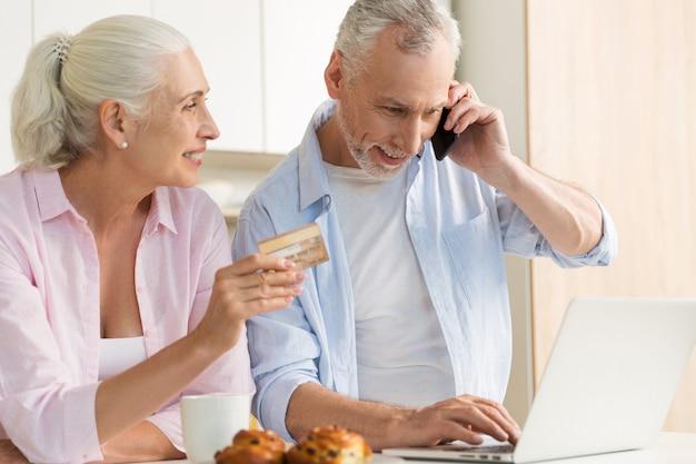 Glimlachende rijpe houdende van paarfamilie die laptop holdingscreditcard gebruiken. Gratis Foto