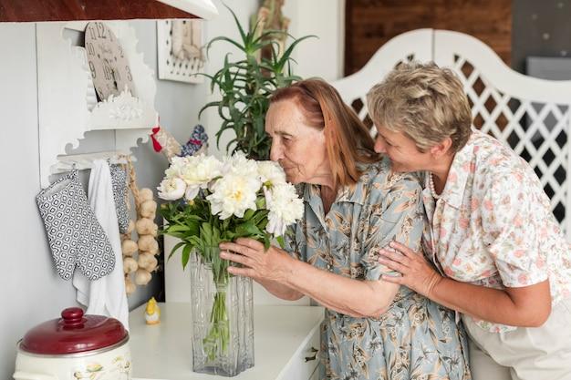 Glimlachende rijpe vrouw die haar moeder bekijken die witte bloemenvaas thuis ruiken Gratis Foto