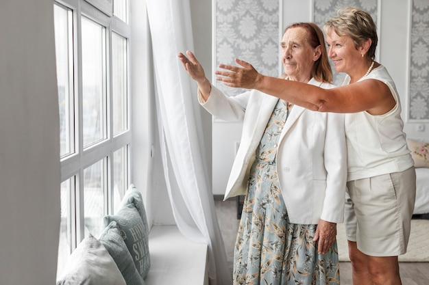Glimlachende rijpe vrouw die iets van venster toont Gratis Foto