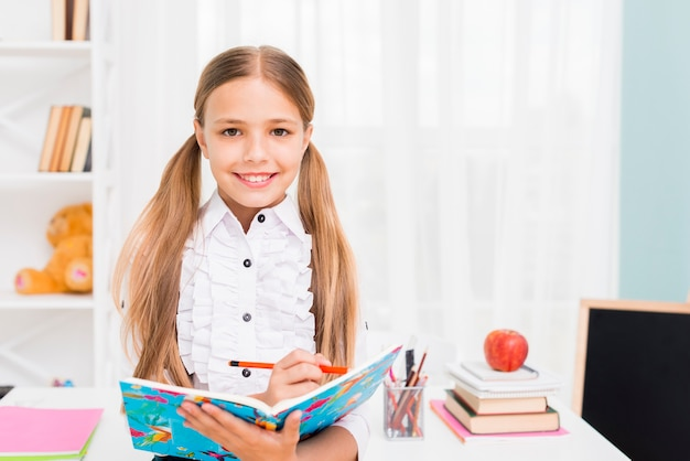 Glimlachende schoolmeisje het schrijven taak met potlood in notitieboekje bij klaslokaal Gratis Foto