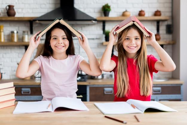 Glimlachende schoolmeisjes onder boekdak Gratis Foto