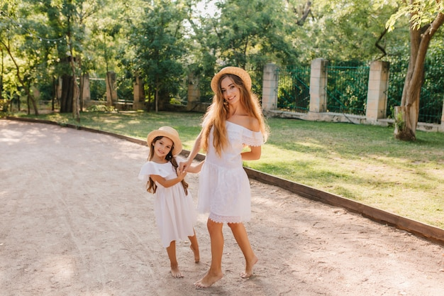 Glimlachende slanke dame in trendy witte jurk poseren in de buurt van dochtertje op straat met ijzeren hek. outdoor portret van schattig meisje en haar slanke moeder in hoed tijd doorbrengen in park. Gratis Foto