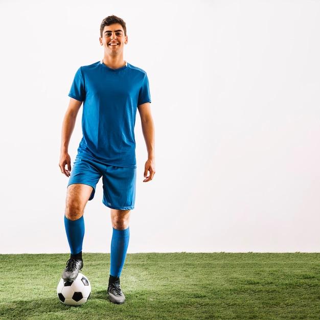 Glimlachende sportman die op bal stapt Gratis Foto