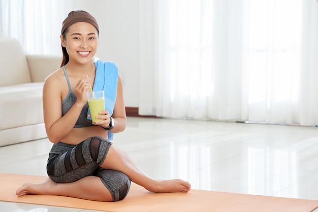 Glimlachende sportvrouw met glas smoothie Gratis Foto