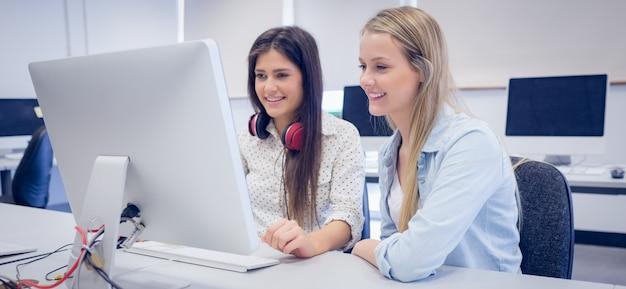 Glimlachende studenten die computer met behulp van bij universiteit Premium Foto