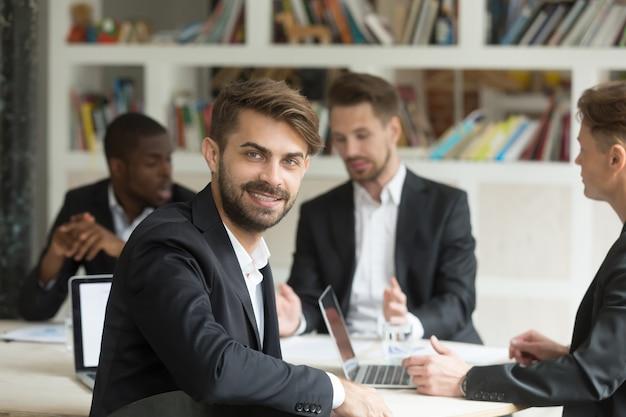 Glimlachende teamleider die camera op groeps collectieve vergadering bekijkt Gratis Foto