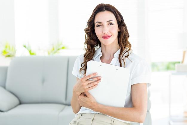 Glimlachende therapeut die haar klembord houdt Premium Foto