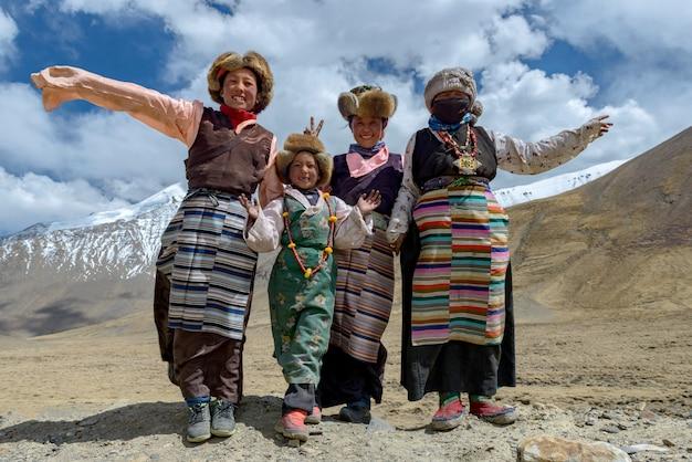 Glimlachende tibetan oude vrouwen en haar familie in nationale kleurrijke kleding die op het de zomergebied blijven in tibet Premium Foto