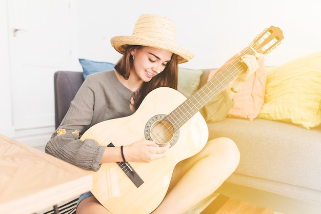 Glimlachende tiener die hoed het spelen gitaar thuis draagt Gratis Foto