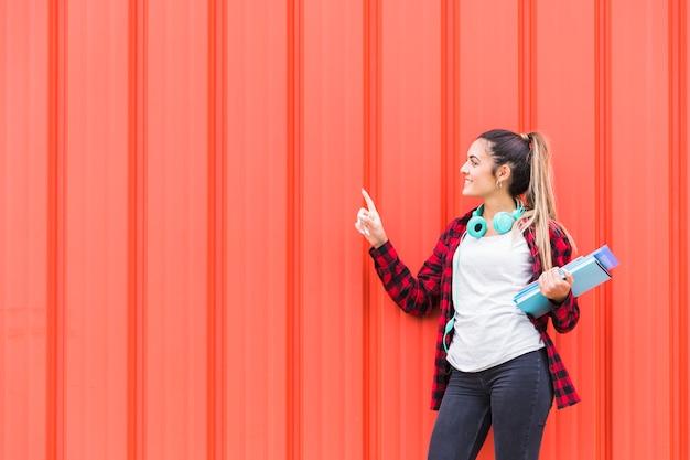 Glimlachende tiener die zich tegen een oranje golfmuur bevindt die haar vinger richt op iets Gratis Foto