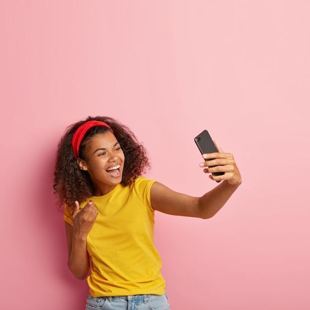 Glimlachende tiener met krullend haar poseren in gele t-shirt Gratis Foto