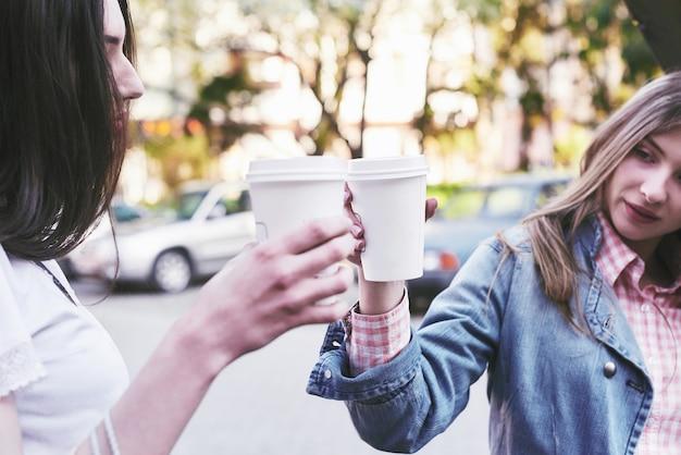 Glimlachende tienermeisjes met koffiekopjes op straat. drankjes en vriendschapsconcept. Gratis Foto
