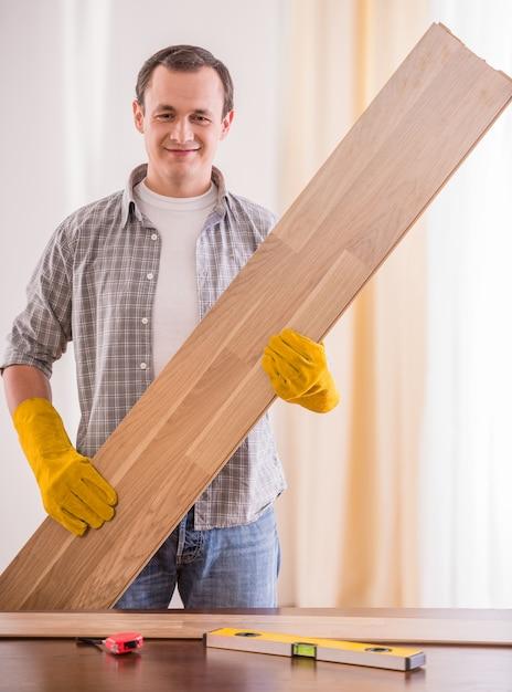 Glimlachende timmerman die in rubberhandschoenen houten planken houden. Premium Foto