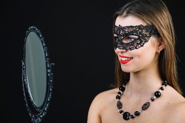 Glimlachende topless vrouw die in carnaval masker in hand spiegel kijkt Gratis Foto