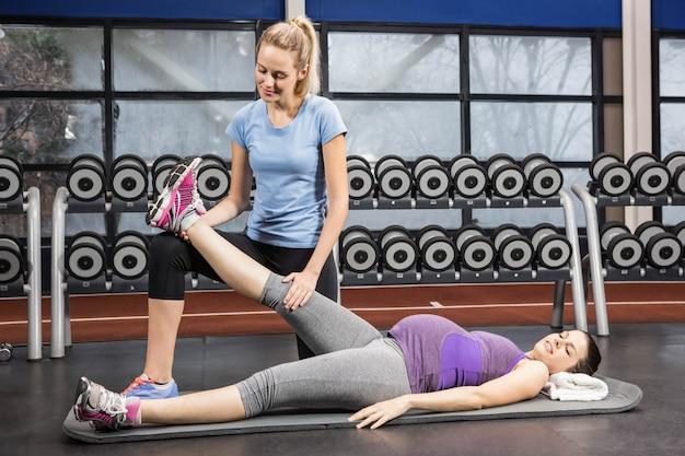 Glimlachende trainer die het been van de zwangere vrouw uitrekken bij de gymnastiek Premium Foto