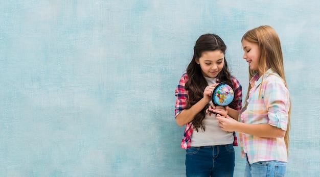 Glimlachende twee meisjes die zich tegen blauwe muur bevinden die kleine bol bekijken Gratis Foto