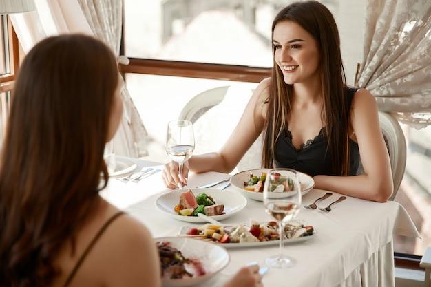 Glimlachende twee vrouwen dineren met witte wijn in het elegante restaurant en kletsen Gratis Foto