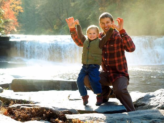 Glimlachende vader met zijn zoon in een park omgeven door groen en een waterval onder het zonlicht Gratis Foto