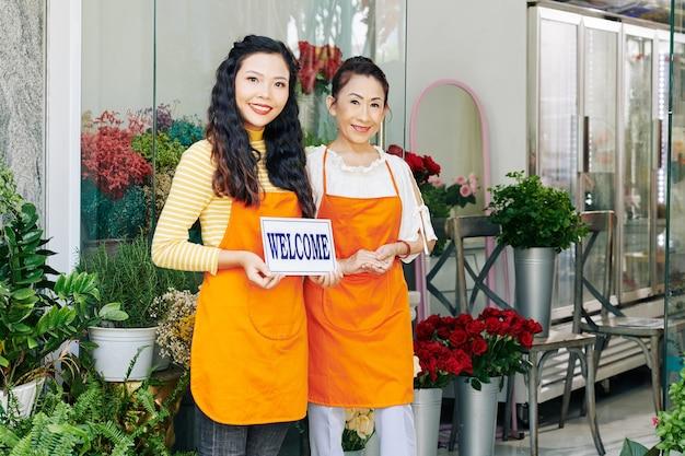 Glimlachende vietnamese moeder en dochter die in oranje schorten bloemenwinkel openen Premium Foto