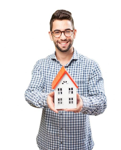 Glimlachende volwassen met een houten huis Gratis Foto