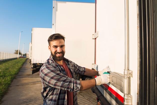 Glimlachende vrachtwagenchauffeur in werkhandschoenen openen of sluiten van de achterdeuren van de vrachtwagenaanhangwagen die goederen controleren voor transport Gratis Foto