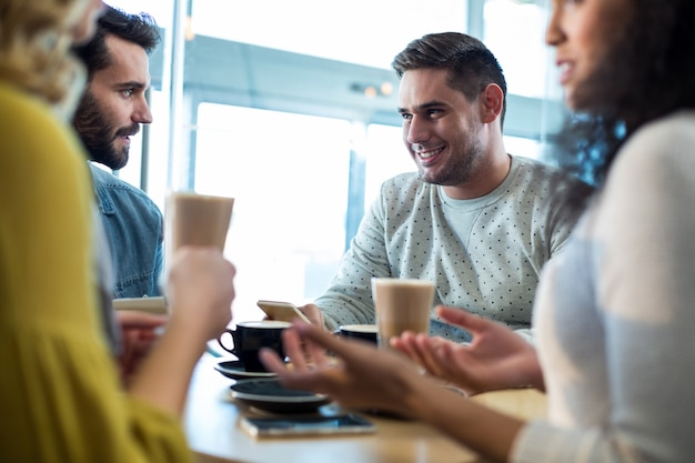 Glimlachende vrienden die een kop van koffie en koude koffie in koffie hebben Premium Foto