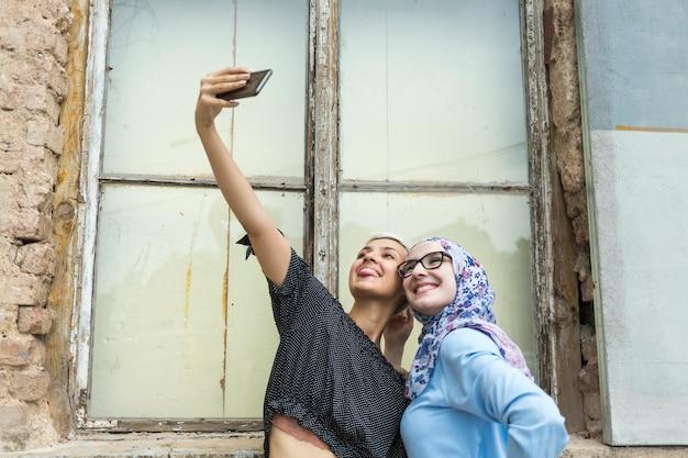 Glimlachende vrienden die een selfie nemen Gratis Foto