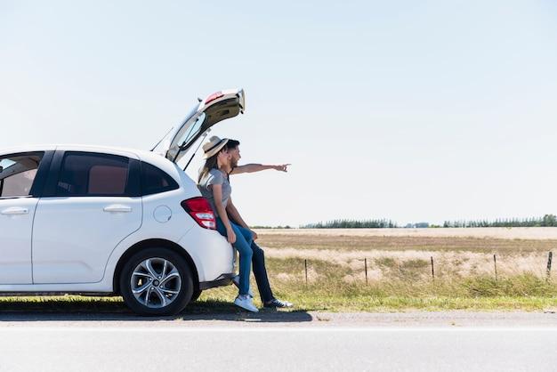 Glimlachende vrienden die op een auto zitten die op iets richten Gratis Foto