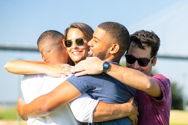 Glimlachende vrienden die op groene weide tijdens zonnige dag samenkomen. vrolijke mensen die in cirkel bij park omhelzen. unie Gratis Foto