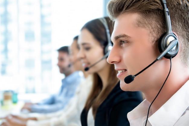 Glimlachende vriendschappelijke mens die in call centrebureau werken met team Premium Foto