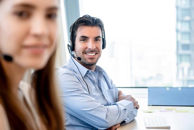 Glimlachende vriendschappelijke spaanse mens die in call centre werkt Premium Foto