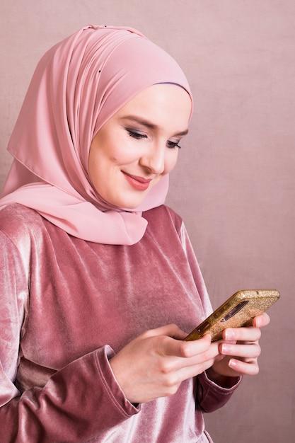Glimlachende vrij moslimvrouw die mobiele telefoon met behulp van Gratis Foto