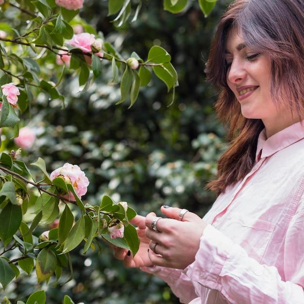 Glimlachende vrouw dichtbij roze bloemen die op groene takjes groeien Gratis Foto