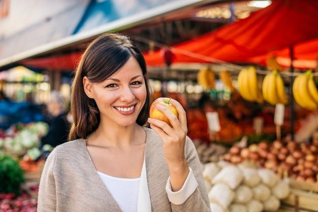 Glimlachende vrouw die een appel houdt bij landbouwersmarkt Premium Foto