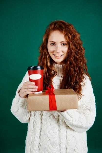 Glimlachende vrouw die gift en koffie geeft Gratis Foto