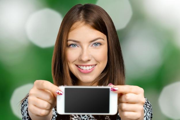 Glimlachende vrouw die het smartphonescherm toont Premium Foto