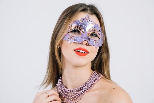 Glimlachende vrouw die het venetiaanse masker van maskeradecarnaval dragen Gratis Foto