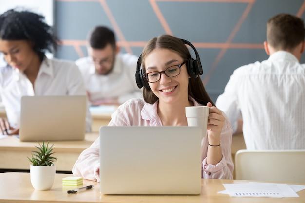 Glimlachende vrouw die hoofdtelefoons draagt die online video tijdens koffiepauze letten Gratis Foto