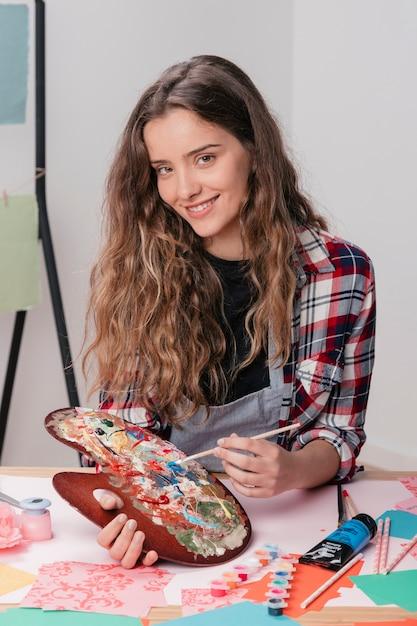 Glimlachende vrouw die houten slordig palet en penseel houdt bekijkend camera Gratis Foto