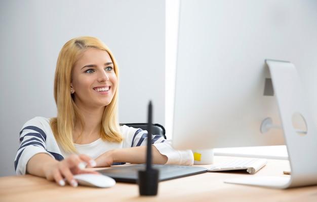 Glimlachende vrouw die in bureau werkt Premium Foto