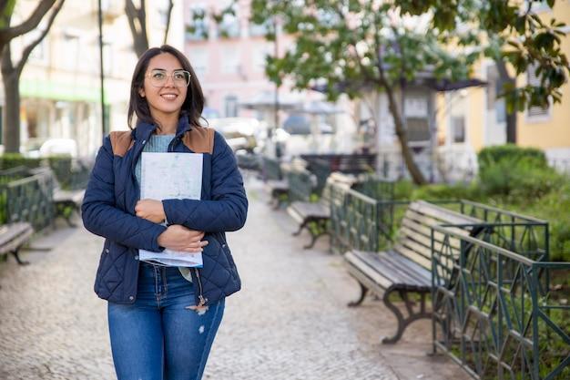 Glimlachende vrouw die in openlucht en gevouwen kaart in openlucht lopen houden Gratis Foto