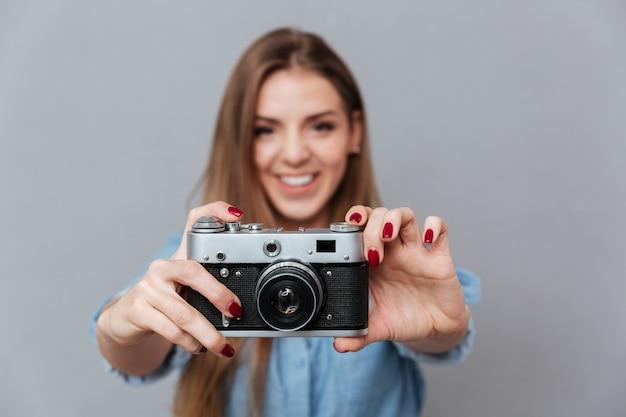 Glimlachende vrouw die in overhemd telefoon op retro camera maakt Gratis Foto