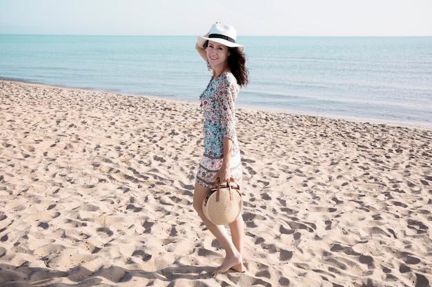 Glimlachende vrouw die op strand loopt Gratis Foto