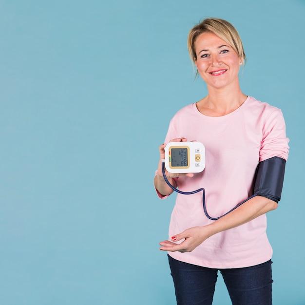 Glimlachende vrouw die resultaten van bloeddruk op het elektrische tonometerscherm toont Gratis Foto