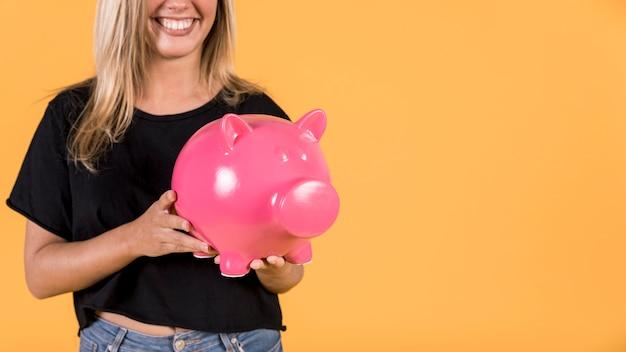 Glimlachende vrouw die roze spaarvarken houdt tegen heldere achtergrond Gratis Foto