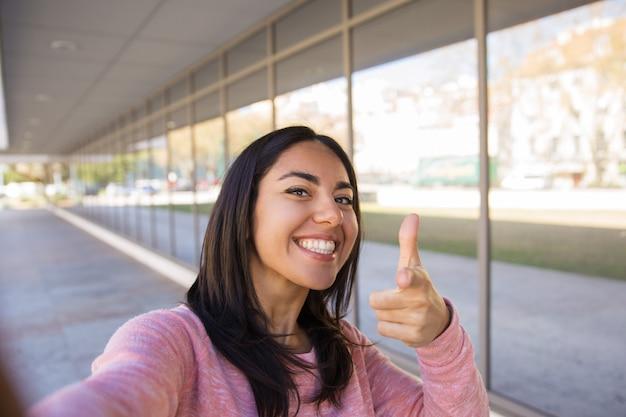 Glimlachende vrouw die selfie foto neemt en in openlucht u richt Gratis Foto