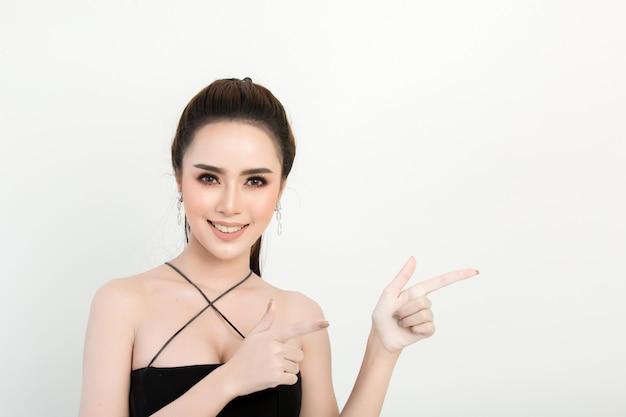 Glimlachende vrouw die vingerkant richt. geïsoleerde portret op wit Gratis Foto