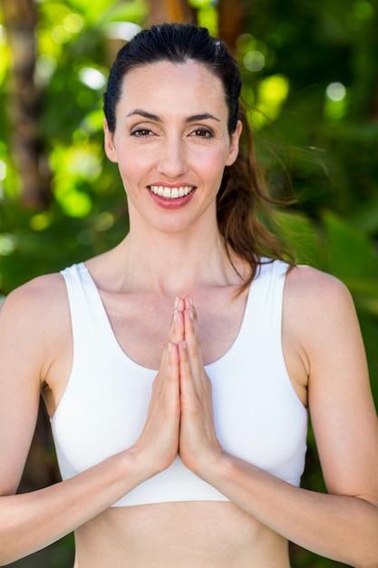 Glimlachende vrouw die yoga op een zonnige dag doet Premium Foto
