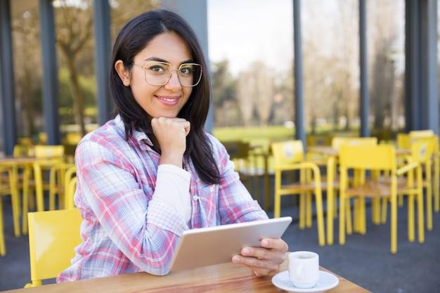 Glimlachende vrouw gebruikend tablet en drinkend koffie in koffie Gratis Foto