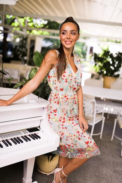 Glimlachende vrouw in de kleurrijke zomerjurk die zich in de buurt van de piano bevindt, staart haitstyle, hakken, mode, buiten, feest, evenement, perfect lichaam, geweldige look, make-up, schattig Gratis Foto